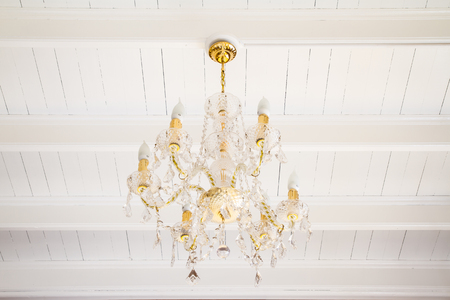 Crystal chandelier on wooden ceiling photo