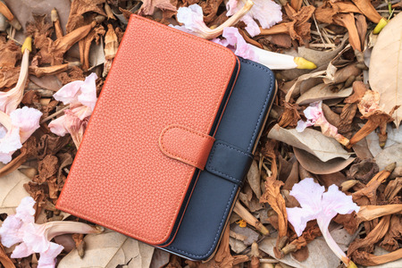 Smartphone leather case cover on dried leafs and flower