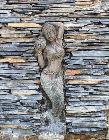 Stucco mermaid on stone layer background photo