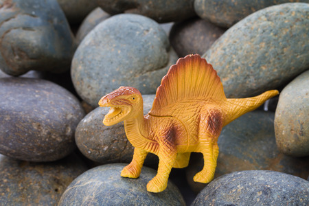 Plastic dinosaur on pebble stone background