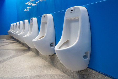 public bathroom: Row of white clean urinals on blue wall in public restroom