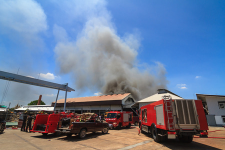 misadventure: Fire truck and burning warehouses with black smoke against blue sky