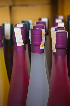 intoxicant: Colorful wine bottles collection on wine rack, with stamp tax label