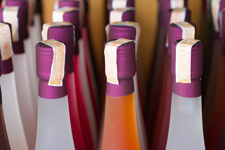 Colorful wine bottles collection on wine rack, with stamp tax label