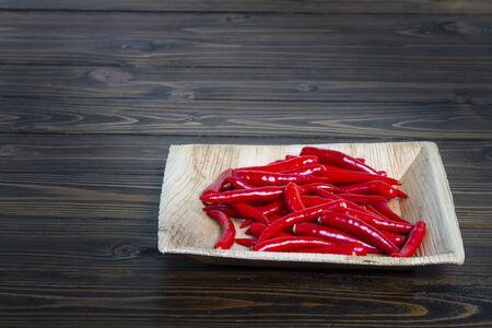 wooden floors: Red peppers in the bark bowl on dark wooden floors