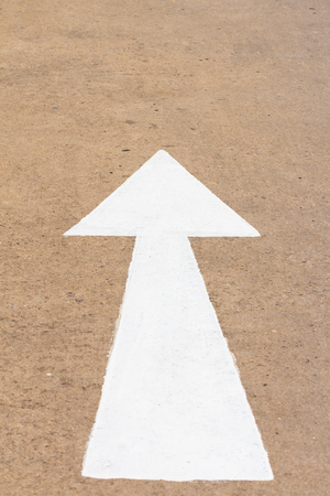 road marking: White arrow sign on a street, road marking Stock Photo