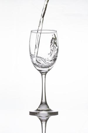water splash: Vertiendo agua en vidrio de la vid en el fondo blanco