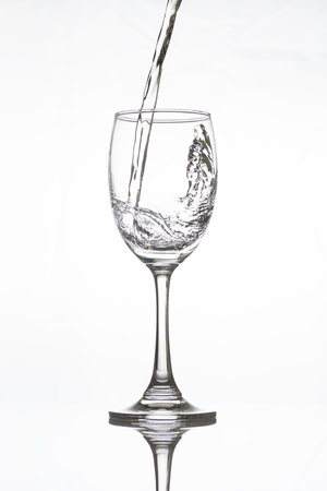 splash background: Water pouring into vine glass on white background
