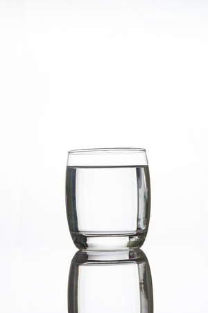 purity: A glass of water with reflection on white background