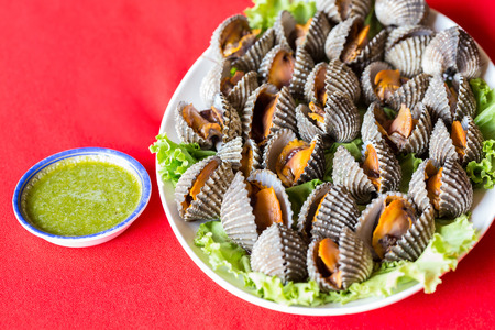 cockles: Boiled fresh cockles on lettuce vegetable for seafood serving Stock Photo