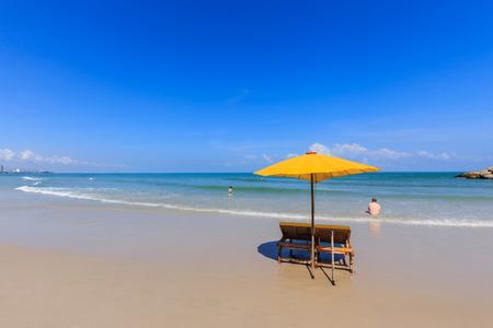hin: Yellow umbrella and wooden chairs on Hua Hin beach, Thailand