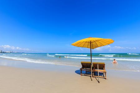 hua hin: Yellow umbrella and wooden chairs on Hua Hin beach, Thailand