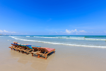 hua hin: Wooden chairs on Hua Hin beach and blue sky, Thailand Stock Photo