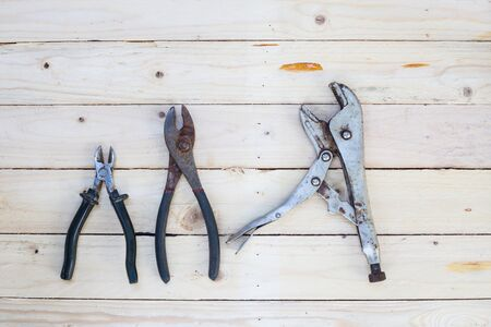 locking: Locking pliers on white wooden background
