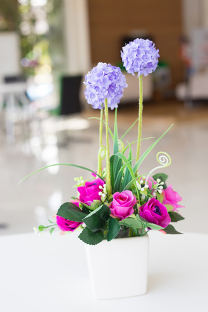 Vases of artificial flowers on the desk