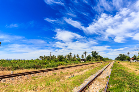 Railroad track in countryside of Thailand with beautiful blue sky