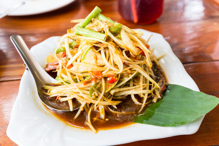 Raw papaya salad well  known in thai is SOM-TAM with banana leaf