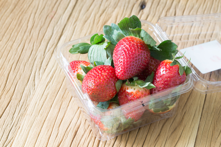 Ripe strawberry in plastic box of packaging on wood table Stock Photo