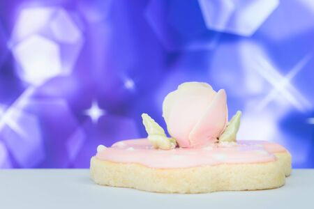 Biscuit top with sugar rose flower on blurry bokeh background