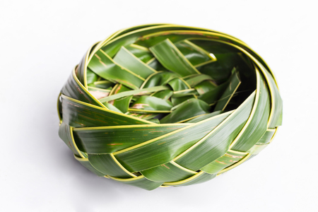 Bowl of coconut leaves on white background