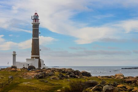 lighthouse in the cable polonio in uruguay surrounded of vegetation green, stones and white houses