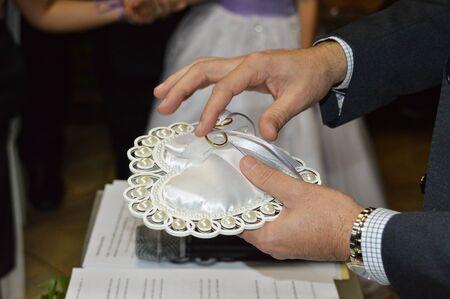Shepherd hand taking wedding rings from cushion top