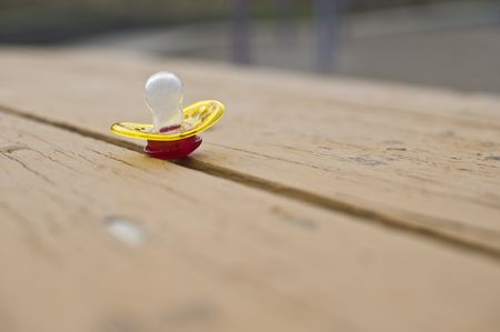 subdue: A forgotten pacifier on a picnic table