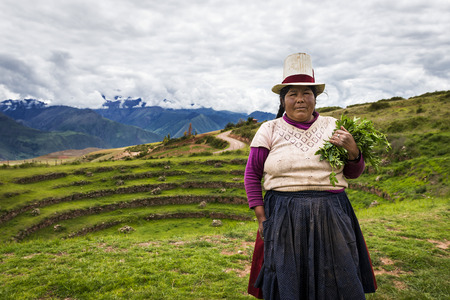 Maras, Peru - December 23, 2013: Peruvian woman in the Moray Inca Terraces, near Maras, in the Sacred Valley, Peru. The Moray terraces are an archaeological site where the Incas built circular terraces believed to be used for studying crops. Local farmers