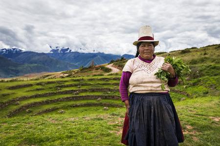 Maras, Peru - 23 december 2013: Peruaanse vrouw in de Moray Inca terrassen, in de buurt van Maras, in de Heilige Vallei, Peru. De Moray terrassen zijn een archeologische site waar de Inca's gebouwd rond terrassen geloofd te worden gebruikt voor het bestuderen van gewassen. lokale boeren