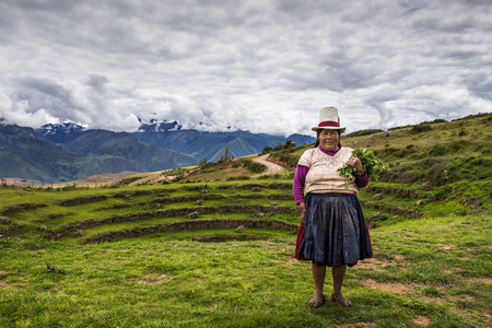 moray: Maras, Peru - December 23, 2013: Peruvian woman in the Moray Inca Terraces, near Maras, in the Sacred Valley, Peru. The Moray terraces are an archaeological site where the Incas built circular terraces believed to be used for studying crops. Local farmers