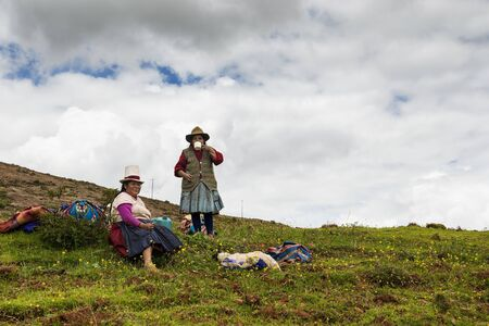 sacred valley: Maras, Peru - December 23, 2013: Two Peruvian women farmers having a break form their work, in the Moray Inca Terraces, near Maras, in the Sacred Valley, Peru. Editorial