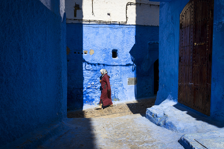 puertas de madera: Chefchaouen, Marruecos - 10 de abril 2016: Una mujer que recorre en una calle de la ciudad de Chefchaouen en Marruecos. Editorial