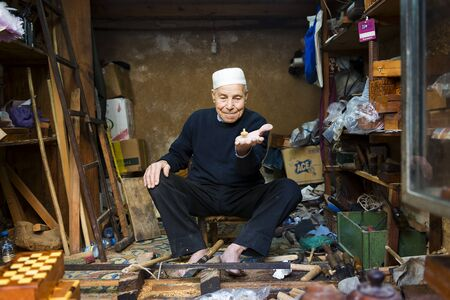 spinning top: Fez, Morocco - April 11, 2016: An artisan showing a spinning top in his shop in the Fez Medina.