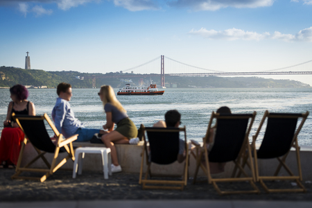 the tagus: People in a esplanade in Lisbon, Portugal, by the Tagus River, with a passenger boat (cacilheiro) crossing the Tagus River; Concept for travel in Portugal Editorial