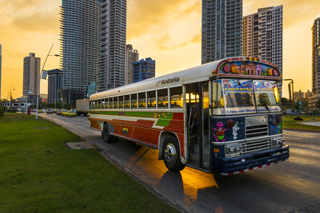 panama city: Panama City, Panama - March 18, 2014: Red Devil Bus (Diablo Rojo) in a street of Panama City at sunset. Red Devil buses are public transports painted in bright colors and symbols.