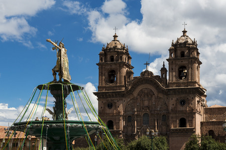 View of the statue of the Inca Emperor with the Church of the Compania de Jesus on the back in Cuzco, Peru