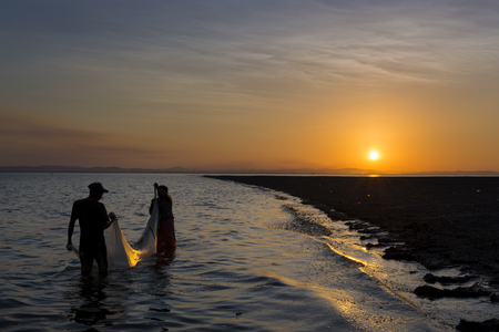 third world: Ometepe Island, Nicaragua - April 7, 2014: Two fisherman fishing in the shores of the Ometepe Island in Lake Nicaragua, Nicaragua, at sunset