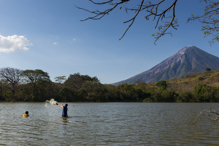 shores: Ometepe Island, Nicaragua - April 7, 2014: Two fisherman fishing in the shores of the Ometepe Island in Lake Nicaragua, with the Concepcion Volcano on the background Editorial