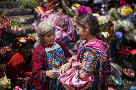 local 27: Chichicastenango, Guatemala - April 27, 2014: Two local women wearing traditional clothing in a street market in the town of Chichicastenango, in Guatemala Editorial