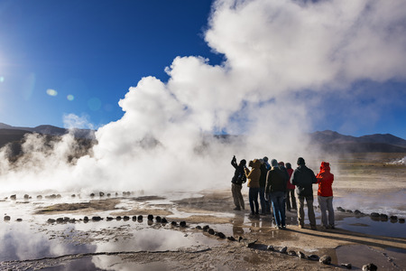 Geysers del Tatio, Chile - November 24, 2013: Tourists watching a geyser in the Geysers del Tatio field in the Atacama Desert, Northern Chile