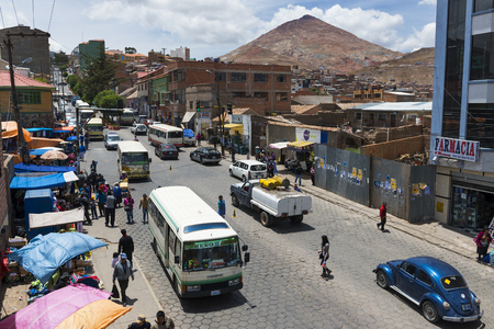 Potosi, Bolivia - November 30, 2013: View of a busy street in the city of Potosi with the Cerro Rico on the background. Potosi is one of the highest cities in the world and it was the major supply of silver for Spain during the colonial era.