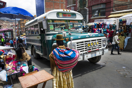 La Paz, Bolivia - December 8, 2013: Busy street scene with a bus and people in the city of La Paz, in Bolivia.