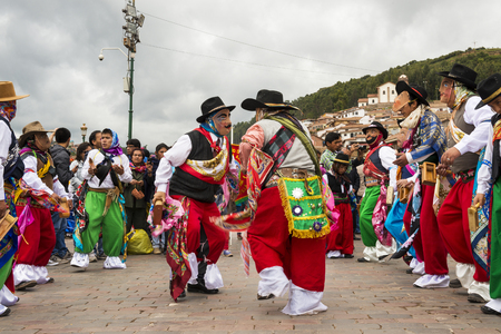 Cuzco, Peru - December 25, 2013: Man wearing traditional clothes and masks dancing the Huaylia in the Christmas day in front of the Cuzco Cathedral in Cuzco, Peru. Редакционное