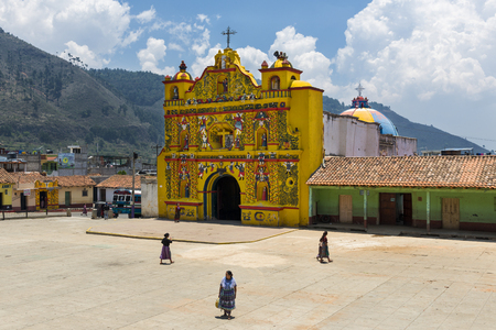 San Andres Xecul, Guatemala - April 29, 2014: The colorful church of San Andres Xecul and three local Mayan woman walking on the street in Guatemala