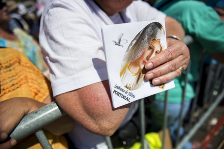 catholic nuns: Fatima, Portugal - May 13, 2014: Detail of a woman holding an image at the Sanctuary of Fatima during the celebrations of the apparition of the Virgin Mary in Fatima, Portugal.