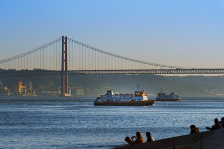 Two passenger boats (Cacilheiros) crossing the Tagus River in Lisbon, Portugal, with the 25 of April Bridge on the background
