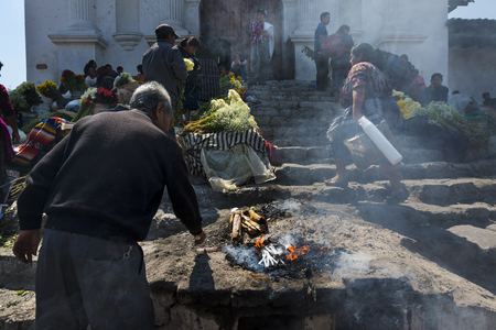 americal: Chichicastenango, Guatemala - April 24, 2014: Man performing an ancient Maya ritual in the stairs of the Santo Tomas Church (Iglesia de Santo Tomas) in the town of Chichicastenango, in Guatemala.