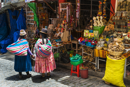 La Paz, Bolivia - December 8, 2013: Two local woman wearing traditional clothing in front of a store in a street of the city of La Paz, in Bolivia