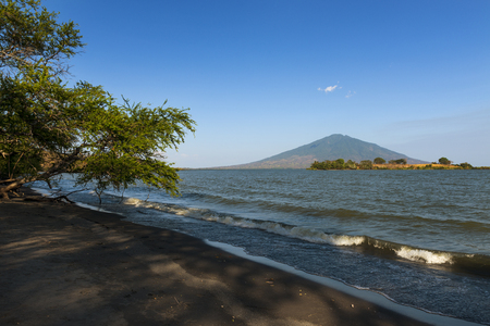 americal: Beach in the Ometepe Island in Lake Nicaragua, with a volcano on the background, in Nicaragua; Concept for travel in Nicaragua and Central America