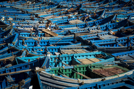 Essaouira, Morocco - April 14, 2016: Two fisherman working in the traditional blue fishing boats docked in the fishing harbour of Essouria in the Atlantic Coast of Morocco.